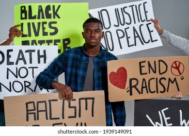 Young african american man standing in middle of placards with anti racist letterings and looking at camera on light background. Stop racism concept
