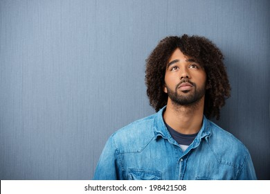 Young African American man standing musing against a grey studio background with copyspace with a serious pensive expression