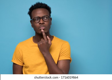 Young african american man, student with finger in mouth in deep thought, isolated on blue background. Negative emotion, facial expression, feelings