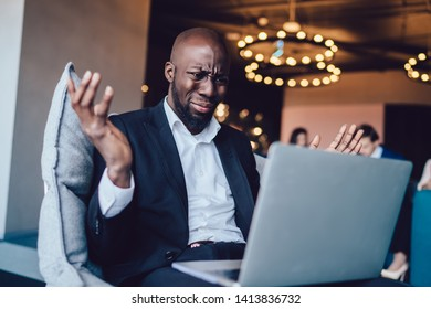 Young African American man in suit sitting in armchair holding hands apart and frowning in misunderstanding using laptop in office