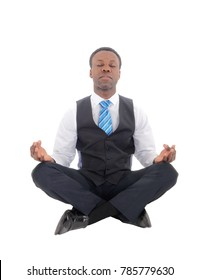 A young African American man in a suit pants and vest and tie sitting