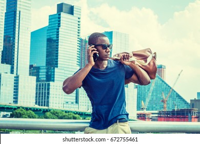 Young African American Man talk on cell phone, traveling in New York in summer, wearing blue T shirt, sunglasses, standing in business district with high buildings, carrying leather bag over shoulder.