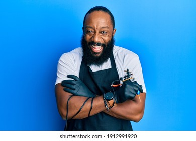 Young african american man tattoo artist wearing professional uniform and gloves holding tattooer machine smiling and laughing hard out loud because funny crazy joke.