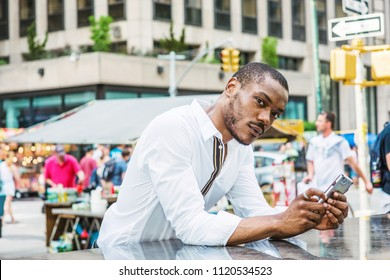 Young African American Man traveling in New York, wearing white shirt, standing by street, texting on cell phone, thinking. Summer Street Fair and Flea Market on center of street on background.
