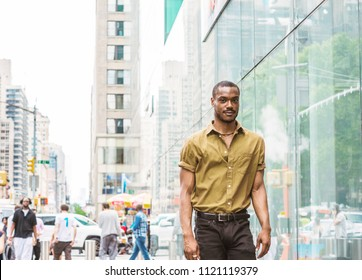Young African American Man traveling in New York, wearing green short sleeve shirt, black pants, walking by glass wall on street in Midtown of Manhattan. People, car, high buildings on background.