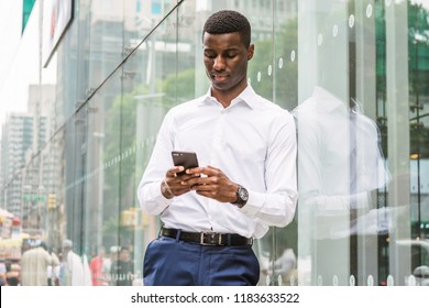 Young African American Man traveling in New York, wearing white long sleeve shirt, wristwatch, standing against glass wall with reflections on street in Middletown of Manhattan, texting on cell phone.