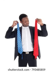 An young African American man tried to decide what tie to wear with