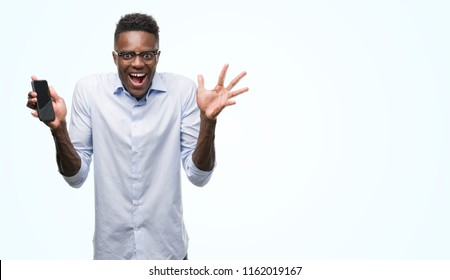 Young african american man using smartphone very happy and excited, winner expression celebrating victory screaming with big smile and raised hands