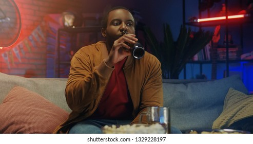 Young African American man watching football game on TV and drinking beer at home. Man  sitting on sofa with bottles of beer.