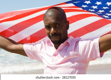 young african american man waving a USA flag on beach