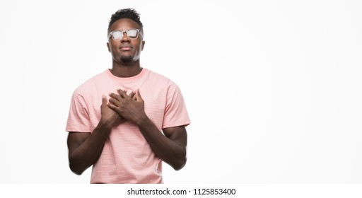 Young african american man wearing pink t-shirt smiling with hands on chest with closed eyes and grateful gesture on face. Health concept.