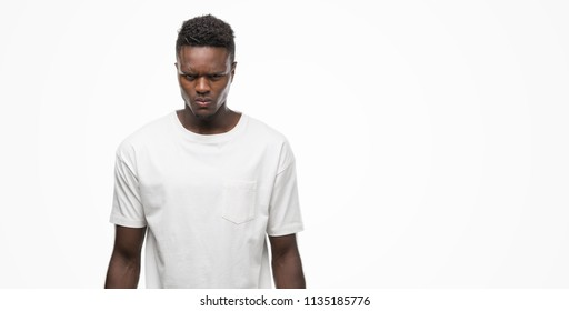 Young african american man wearing white t-shirt skeptic and nervous, frowning upset because of problem. Negative person.