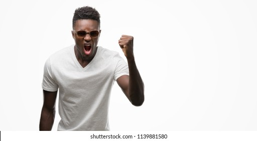Young african american man wearing sunglasses annoyed and frustrated shouting with anger, crazy and yelling with raised hand, anger concept