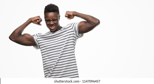 Young african american man wearing glasses and navy t-shirt showing arms muscles smiling proud. Fitness concept.