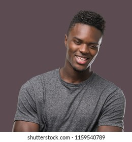 Young african american man wearing grey t-shirt happy face smiling with crossed arms looking at the camera. Positive person.