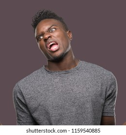 Young african american man wearing grey t-shirt crazy and mad shouting and yelling with aggressive expression and arms raised. Frustration concept.