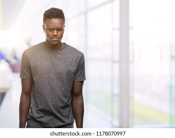 Young african american man wearing grey t-shirt skeptic and nervous, frowning upset because of problem. Negative person.