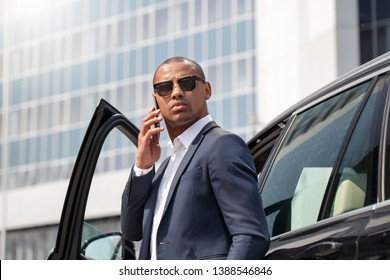 Young african american man wearing sunglasses standing leaning on car calling to business partner on smartphone looking aside serious