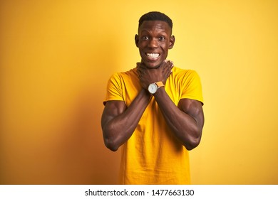 Young african american man wearing casual t-shirt standing over isolated yellow background shouting suffocate because painful strangle. Health problem. Asphyxiate and suicide concept.