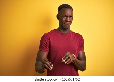 Young african american man wearing red t-shirt standing over isolated yellow background disgusted expression, displeased and fearful doing disgust face because aversion reaction. With hands raised.