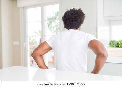 Young african american man wearing casual white t-shirt sitting at home standing backwards looking away with arms on body
