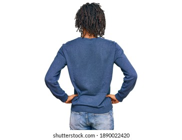 Young african american man wearing casual winter sweater standing backwards looking away with arms on body