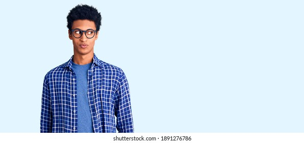Young african american man wearing casual clothes and glasses smiling looking to the side and staring away thinking.