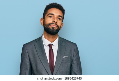 Young african american man wearing business clothes relaxed with serious expression on face. simple and natural looking at the camera.