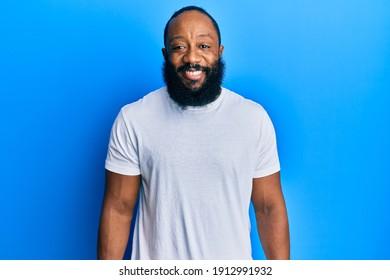 Jeune homme afro-américain portant un t-shirt blanc décontracté avec un sourire joyeux et frais sur le visage. chanceux.
