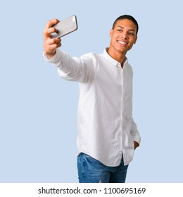Young african american man with white shirt taking a selfie with the mobile on isolated blue background