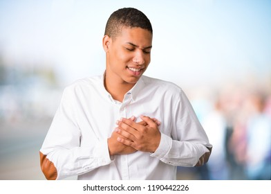 Young african american man with white shirt having a pain in the heart. Heart attack on unfocused outdoor background