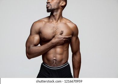 Young african american man with white shirt having a pain in the heart. Heart attack isolated on gray background