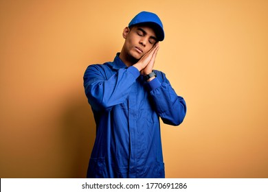 Young african american mechanic man wearing blue uniform and cap over yellow background sleeping tired dreaming and posing with hands together while smiling with closed eyes.