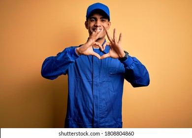 Young african american mechanic man wearing blue uniform and cap over yellow background smiling in love doing heart symbol shape with hands. Romantic concept.