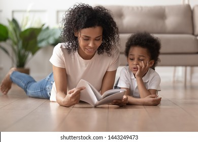 Young african American mom lying on floor with cute toddler boy reading book at home together, black loving mother or nanny enjoy spending time with little son learning look at pictures in textbook