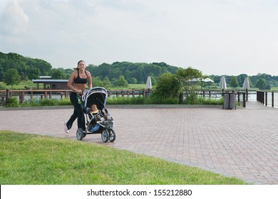 Young African American Mom Running Outdoor with Little Boy in Stroller Under Morning Sun Light