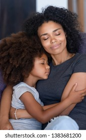 Young African American mommy relax on couch hugging little cute daughter falling asleep together, loving black mom cuddle with small kid, caressing folding to breast, have close tender moment