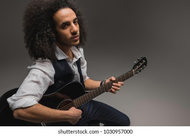 young african american musician playing acoustic guitar