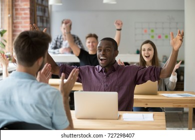 Young african american office worker throws hands in air celebrating achievement at work. Coworkers around cheering and clapping hands. Rewarding outcome, received promotion, achieved success concept.