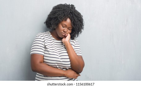 Young african american plus size woman over grey grunge wall thinking looking tired and bored with depression problems with crossed arms.