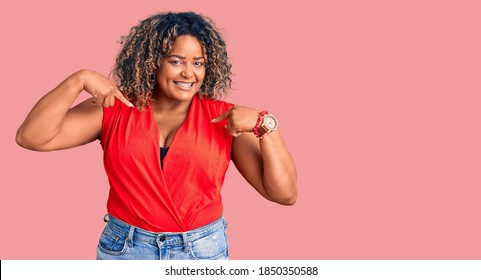 Young african american plus size woman wearing casual style with sleeveless shirt looking confident with smile on face, pointing oneself with fingers proud and happy.