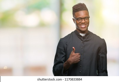 Young african american priest man over isolated background doing happy thumbs up gesture with hand. Approving expression looking at the camera with showing success.