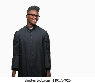 Young african american priest man over isolated background looking away to side with smile on face, natural expression. Laughing confident.