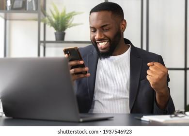 Junge afrikanische Amerikaner lesen unerwartete gute Nachrichten über Smartphone