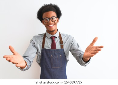 Young african american shopkeeper man wearing apron glasses over isolated white background looking at the camera smiling with open arms for hug. Cheerful expression embracing happiness.
