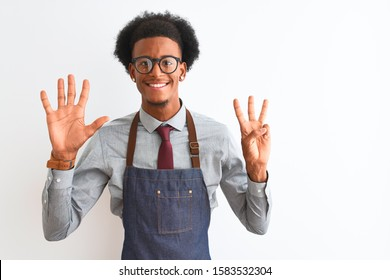 Young african american shopkeeper man wearing apron glasses over isolated white background showing and pointing up with fingers number eight while smiling confident and happy.