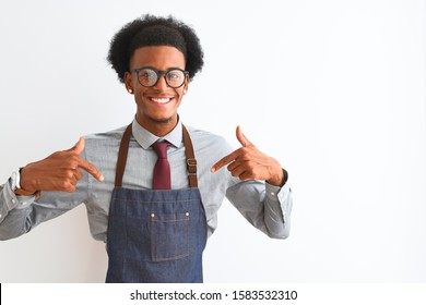 Young african american shopkeeper man wearing apron glasses over isolated white background looking confident with smile on face, pointing oneself with fingers proud and happy.
