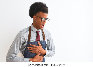Young african american shopkeeper man wearing apron glasses over isolated white background with hand on stomach because indigestion, painful illness feeling unwell. Ache concept.