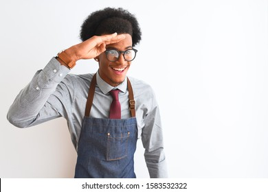 Young african american shopkeeper man wearing apron glasses over isolated white background very happy and smiling looking far away with hand over head. Searching concept.