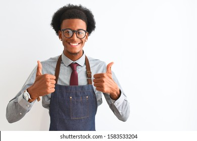Young african american shopkeeper man wearing apron glasses over isolated white background success sign doing positive gesture with hand, thumbs up smiling and happy. Cheerful expression and winner